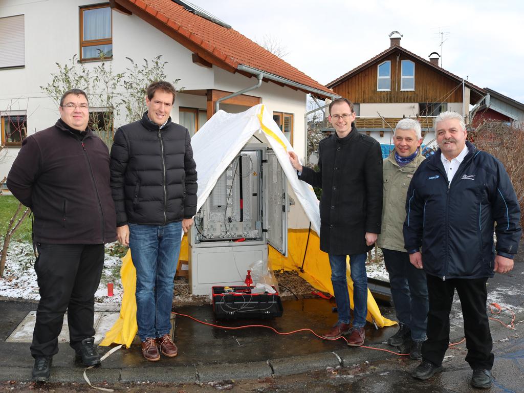 Die Verantwortlichen des Projekts stehen vor dem Verteilerkasten, der die Hauptleitung des Glasfasernetzes aufteilt zu den einzelnen Haushalten.